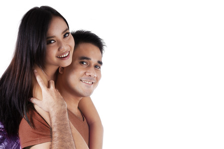 filipino adult: Portrait of smiling couple embracing on white background