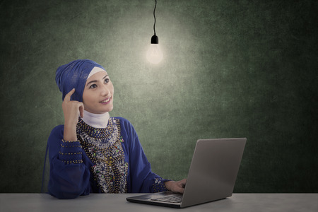 Beautiful female muslim under light bulb has an idea photo