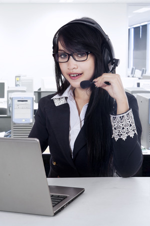 Female customer support operator with headset and smiling at office photo