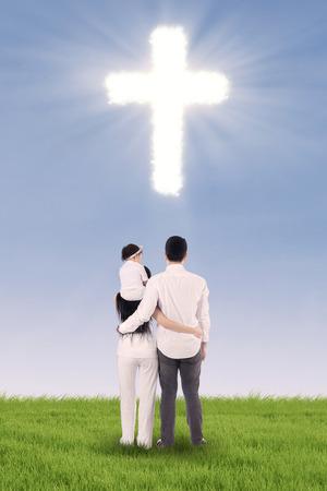 familia cristiana: Familia cristiana que se divierten en campo verde con el símbolo de la cruz
