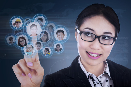 Close-up of businesswoman choosing few candidates on blue touchscreen photo