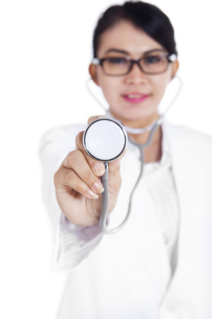 Smiling female doctor showing a stethoscope, isolated on white background photo