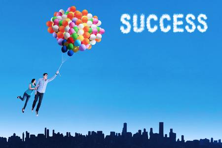realiseren: Gelukkig paar vliegen met ballonnen om hun droom te realiseren