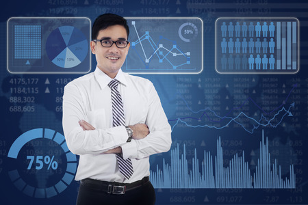 asian businessman: Confident modern businessman standing in front of business graph