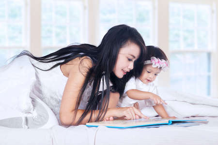 bonding: Close-up of a mother and baby girl reading book story on bed Stock Photo