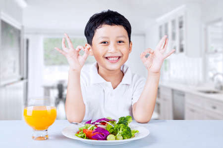 kids eating: Cute boy making OK gesture while having salad, shot in the kitchen