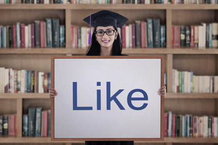 graduation gown: Woman in graduation gown showing like sign on board