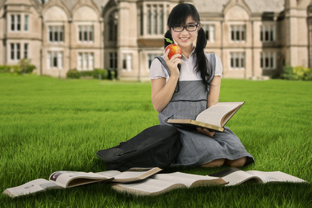 Female student holding a red apple while studying outdoors photo