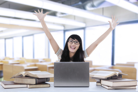library student: Cheerful female student expressing happiness in the library Stock Photo