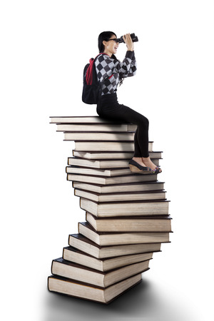 Female student sitting on the stack of books while looking for future by using binoculars photo