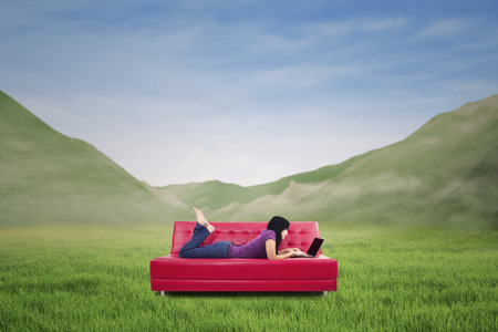 Young woman lying on couch with laptop - shot outdoor with mountain view photo