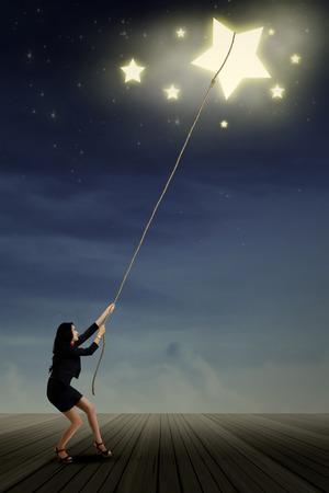 proposito: Retrato de joven empresaria tomando estrellas del cielo espacio