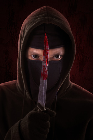 Danngerous killer standing in the dark and holding a bloody knife photo