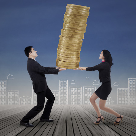 Portrait of business team carrying gold coins symbolizing as high profit photo