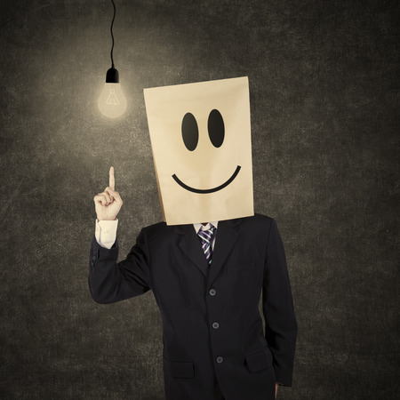 Businessman with cardboard head having a bright idea while pointing at bright lightbulb photo