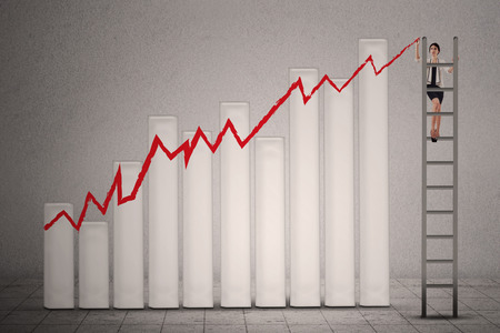indian professional: Businesswoman is climbing ladder while drawing profit chart Stock Photo