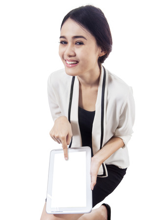 Asian woman showing blank screen of portable tablet. isolated on white photo