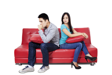 Couple sitting back to back after a fight on the sofa photo