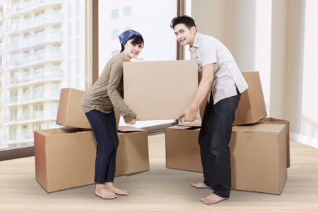 Young asian couple unpacking cardboard in new home photo