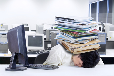Depressed fat businessman with a pile of documents on his head at office