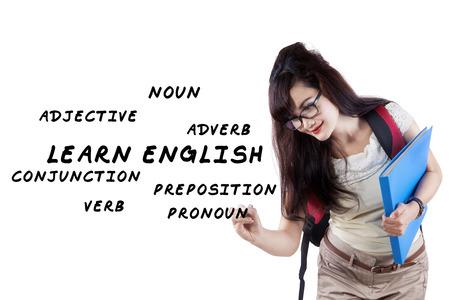 noun: Female student writes english language materials on whiteboard