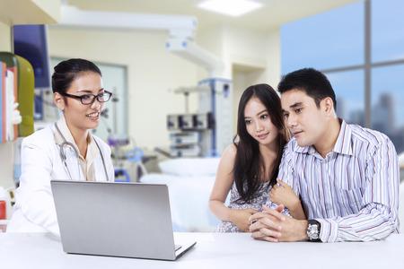Asiatische Frauen Arzt Erläuterung des Check-up Ergebnis schwangeren Frau in Arztzimmer