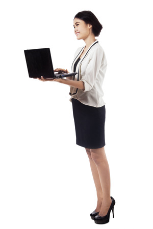 Businesswoman working with a laptop isolated on white  photo