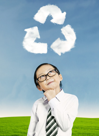 Little kid thinking about recycling with recycle symbol above his head photo