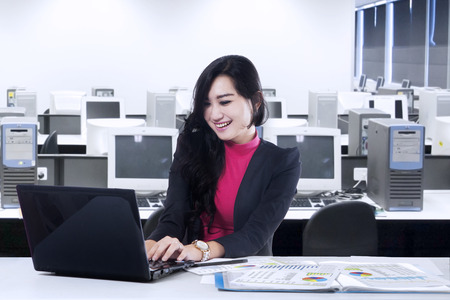 Happy business woman working on laptop computer at office photo