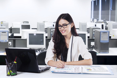 Portrait of beautiful smiling businesswoman sitting at office photo