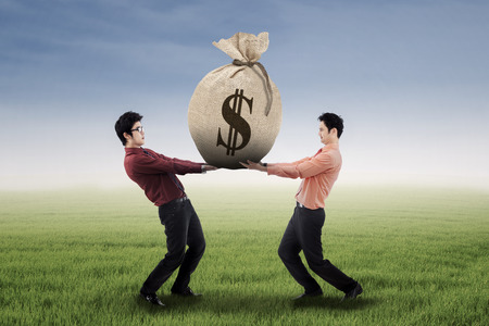 sackful: Two business people carrying a money bag with US dollar sign Stock Photo