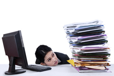 overwork: Businesswoman looking at pile of documents on the desk Stock Photo