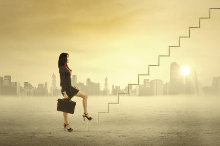climbing stairs: Joven empresaria caminando en las escaleras de �xito