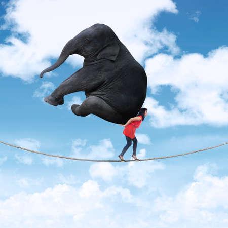 krachtige vrouw: Portret van een vrouw het dragen van zware olifant tijdens het lopen op het touw Stockfoto