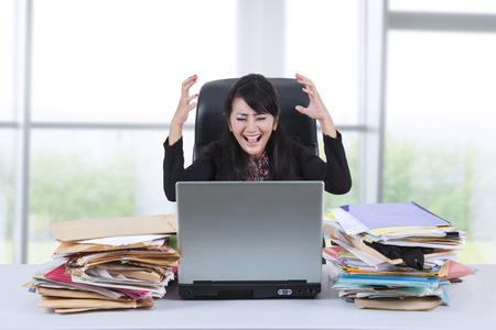 stressful: Portrait of stressful businesswoman screaming in the office Stock Photo