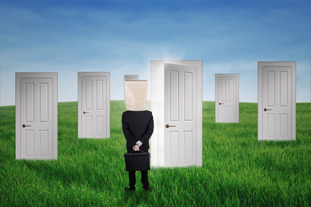 Anonymous businessman standing in front of opportunity doors on the green field photo