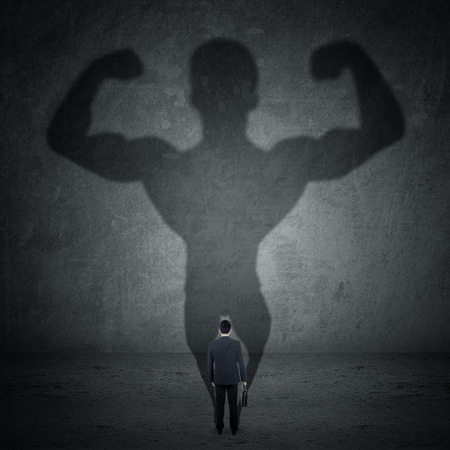 Business man casting a shadow of an athlete - business and career strength concept photo