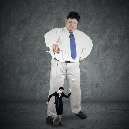 Businesswoman hanging on string and controlled by a businessman photo