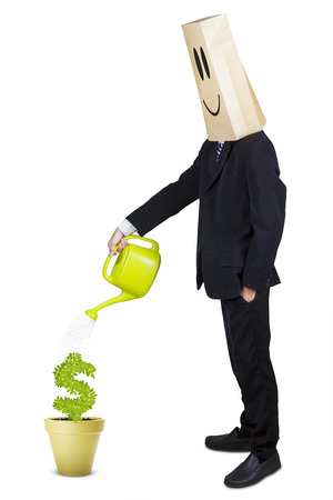 Anonymous businessman watering plant in pot with can photo