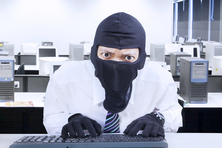 Businessman wearing mask stealing information in office photo