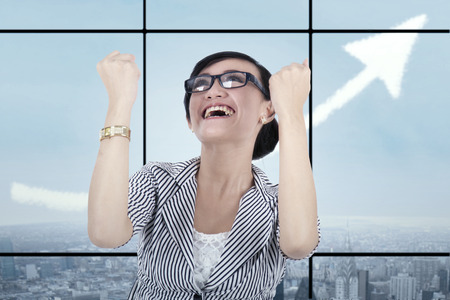 Businesswoman celebrating success in front of a window with an upward arrow photo