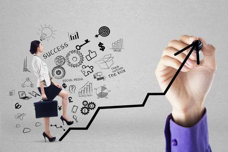 Businesswoman climbing upward chart to gain her business target by following businessmans hand photo