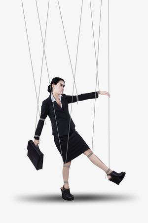obedecer: Empresaria que cuelgan en cadenas como marioneta. aislado en blanco