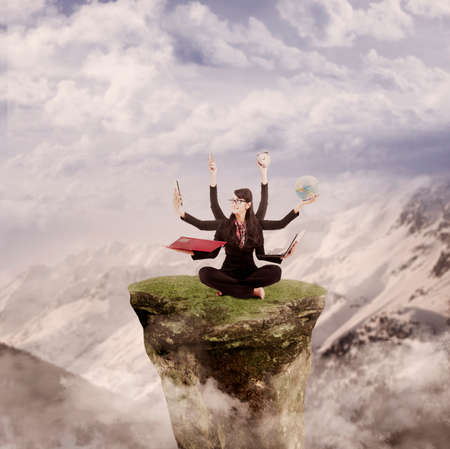 Businesswoman is juggling many tasks on top of a mountain photo
