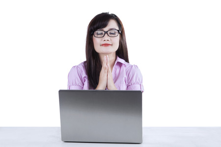 Asian businesswoman praying while working in office photo