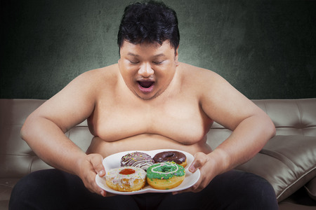 Cheerful fat man looking at donuts while sitting on the sofa at home photo