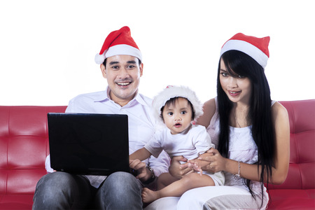 daugther: Christmas family playing with laptop computer, sitting on red sofa
