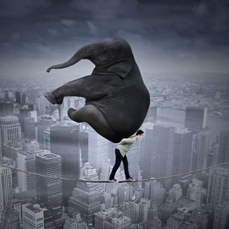 work load: Portrait of businessman carrying heavy elephant while walking on the rope over a big city