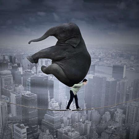 trasloco: Ritratto di uomo d'affari che trasportano elefante pesante mentre si cammina sulla corda sopra una grande citt� Archivio Fotografico