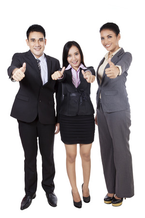 Happy business people giving thumbs up on white background photo